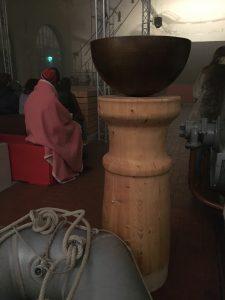"""Hier trägt eine Rundsäule aus Brettschichtholz das Taufbecken im Theaterstück """"Die Maßnahme"""" auf dem Brechtfestival 2017 in Augsburg."""